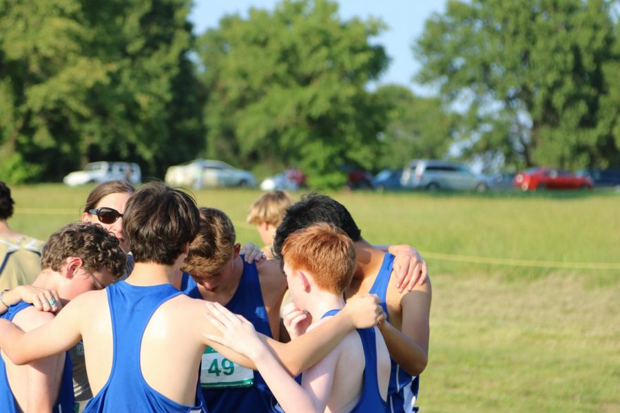 Left to Right: Sophomore Jude Black, faculty member Kara Schrader, freshman Jason Meschke, senior Henry Nelson, freshman Sam Jackson and sophomore Diego Klish huddle before a cross country meet. This meet was the first meet for majority of the varsity boy's team.