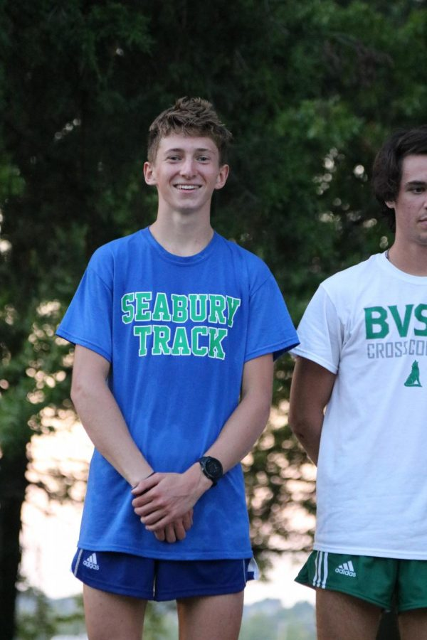 Senior Henry Nelson poses for a photo during a cross country medal ceremony. Nelson has placed first in all the meets he has run.