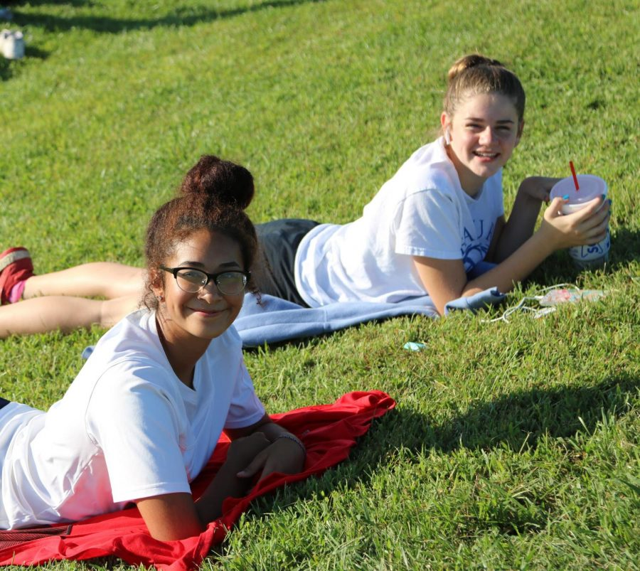Eighth graders Helena Gutierrez-Gibbs and Vivian Hill cheer on the varsity boys' soccer game. Despite the lack of seating on the field, they still found a comfortable way to view the game.