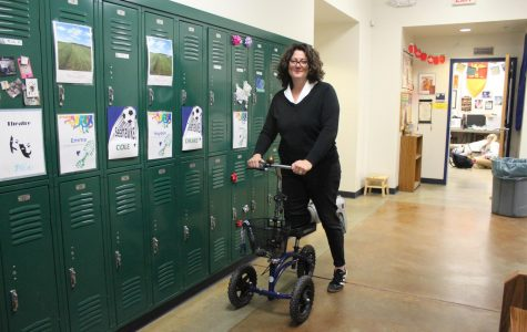 Faculty member Cris Bryan rolls down the hall with her new boot scooter. Bryan has had a boot since April 25th