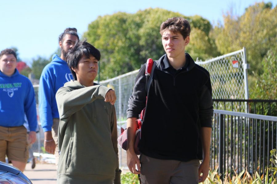 Juniors Bruce Xu and Brayden Shumaker fight for sidewalk space. The students were forced to fight for their space on the sidewalk due to crowding from the vehicles and bushes on opposing sides of the path.