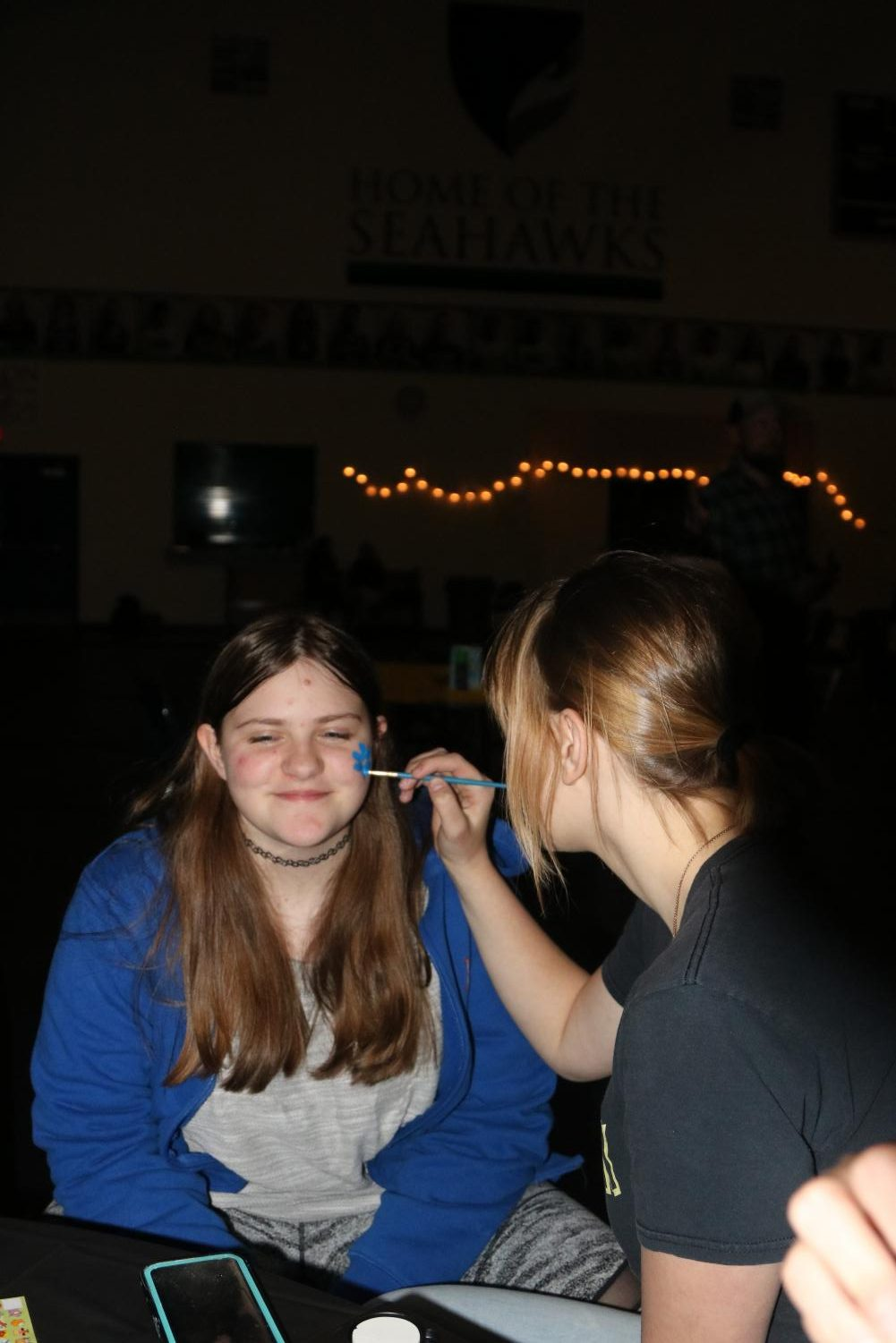 Alesia Brovtcnya paints Elizabeth Allen face during Carnival. Carnival this year was held in the gym.