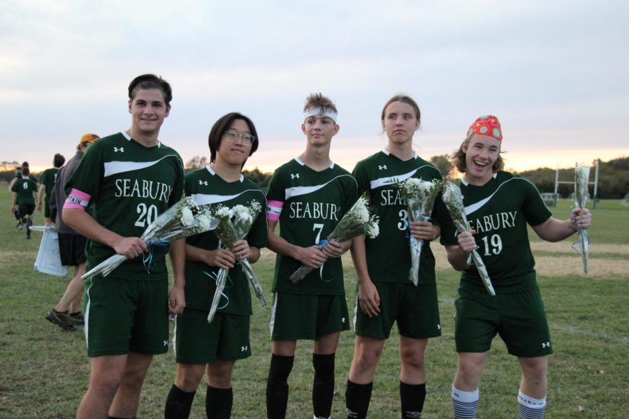 Seniors Sam Bayliss, Jinu Jung, Freddy Comparato, Aidan Atwood-Blaine and Sam Hindman smile for a photo during soccer senior night. All the seniors were given flowers and had a speech dedicated to them after the game.