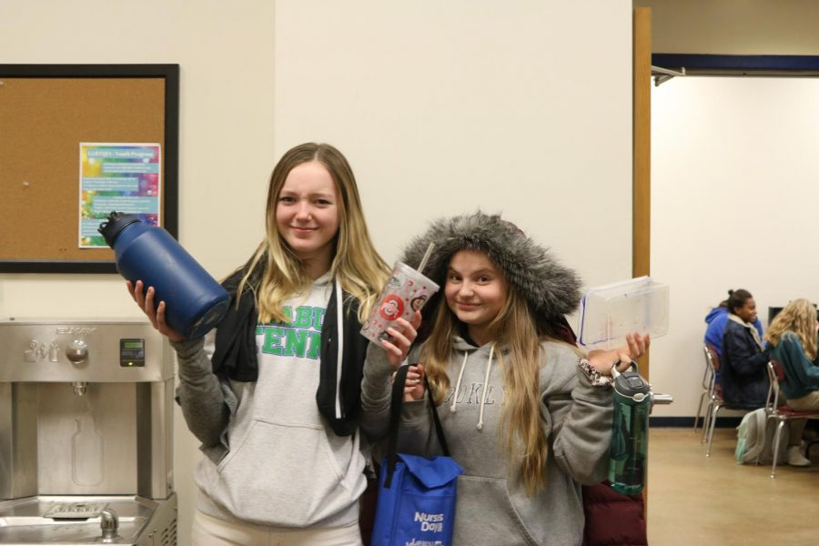 Eighth graders Alexandra Terry and Eve Tuckel pose with lost and found items. Student's missing items can usually be found in the bins in front of Ms. Czarnecki's room... unless someone else took them first