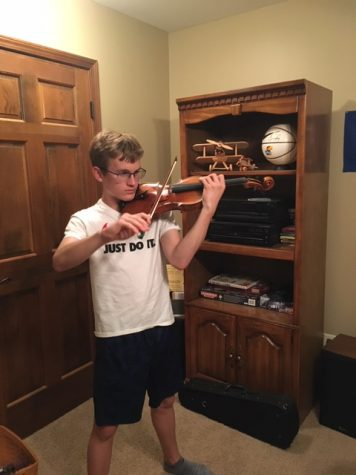 Freshman Noah Luke practice his violin. Luke has played violin for the Topeka Debut Youth Orchestra and the Philharmonic Orchestra of Kansas City
