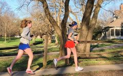 Eighth graders Campbell Helling and Isabelle Pro run through a neighborhood. Pro showed huge dedication to running by running a half marathon on her own when her race was canceled.