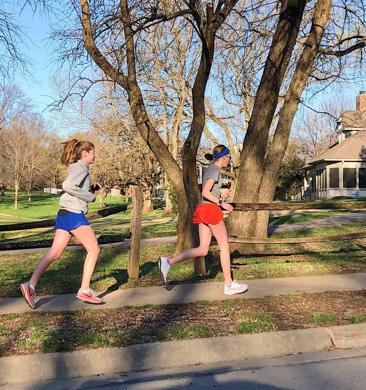 Eighth+graders+Campbell+Helling+and+Isabelle+Pro+run+through+a+neighborhood.+Pro+showed+huge+dedication+to+running+by+running+a+half+marathon+on+her+own+when+her+race+was+canceled.